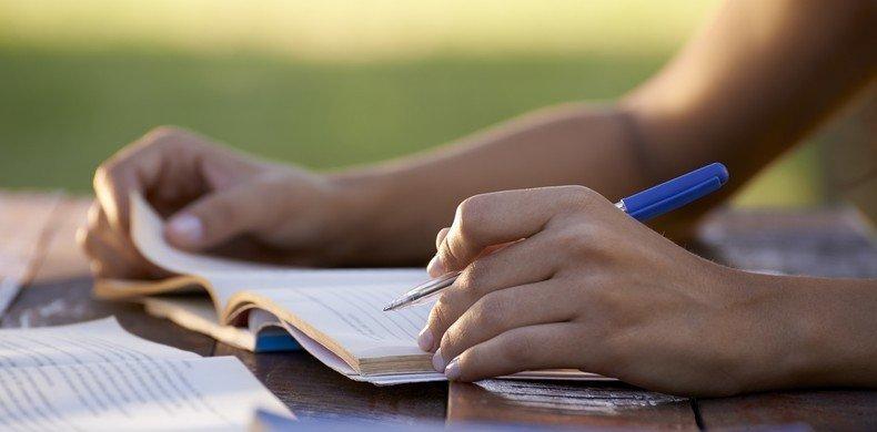 Concurseiro estudando com caderno e caneta