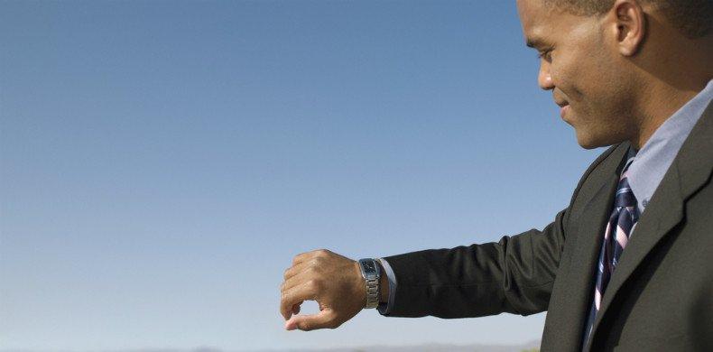 homem de terno olhando o relógio