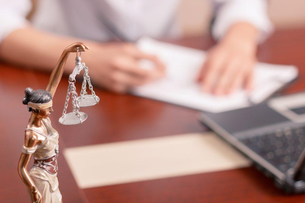 Advogado assinando papéis com a estátua da justiça